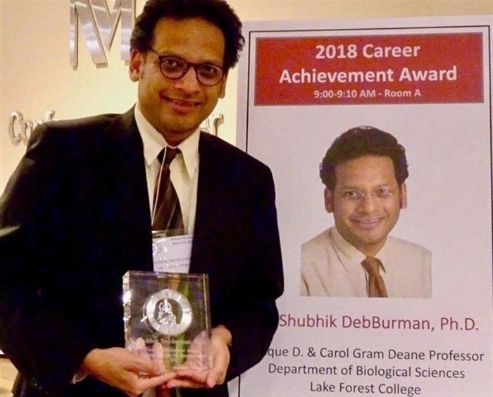 Professor holding his career achievement award trophy