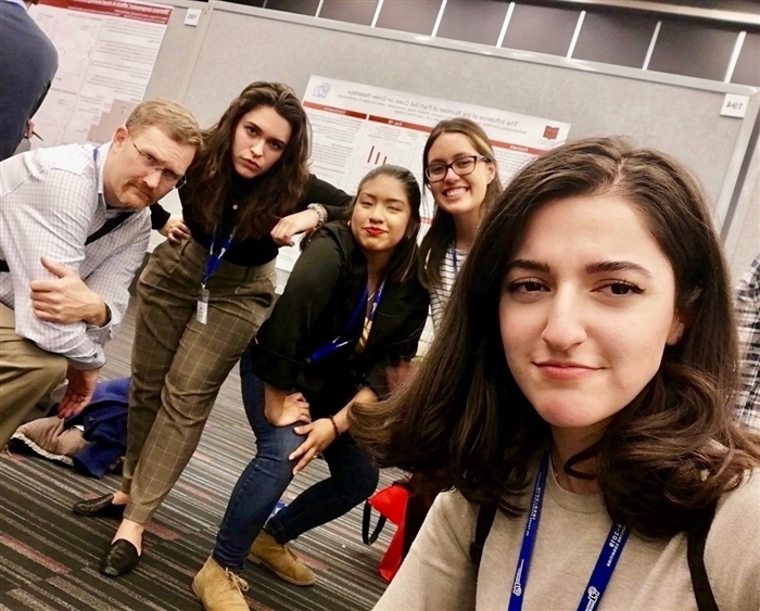 professor and four students mugging for selfie in front of their research poster