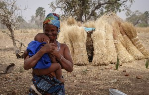 A Fulani, nomadic ethnic group of cattle herders in West Africa, mother holds her baby. It is common for women to adorned in colorful fabrics and jewelry.