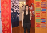 "Tzi-Ching ""Anica"" Lin '13 poses in the Sonnenschein Gallery, where her five screen-printed textiles are temporarily ..."