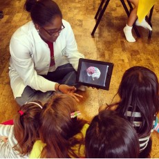 Kim Diah '13 teaches children about the brain with art as part of a volunteer experience with the Palm Beach chapter of ...