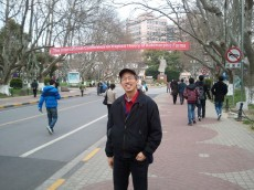 Professor of Mathematics David Yuen poses in front of the conference banner at the University of Tongji, Shanghai.