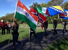 Students carry flags from their countries