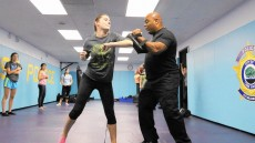 Sgt. Dwight Davis demonstrates self-defense moves to Lake Forest College senior Mara Negru during a class at the Lake Fore...