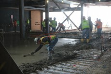 Workers smooth the just-poured concrete to create floors in the science center addition.