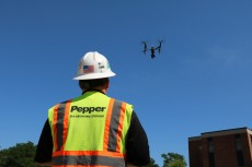 A drone operator launches a camera-equipped drone to circle the Lillard Science Center construction project, capturing ima...