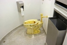 "An 18-karat-gold toilet, titled ""America,"" by the sculptor Maurizio Cattelan in a restroom of the Guggenheim Museu..."