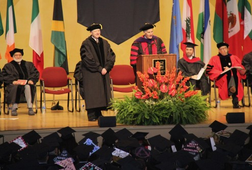 President Schutt confers an honorary Doctor of Liberal Arts on Gary Johnson (standing, left). Teepu Siddique (seated, left) received a Doctor of Science.